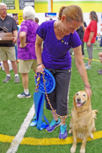 Donna Schmidt and her Golden Retriever Jade with large high in trial ribbon